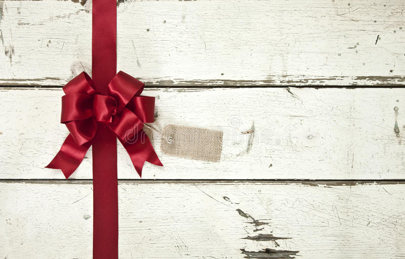 Red Christmas bow and ribbon on old painted white wood background stock image