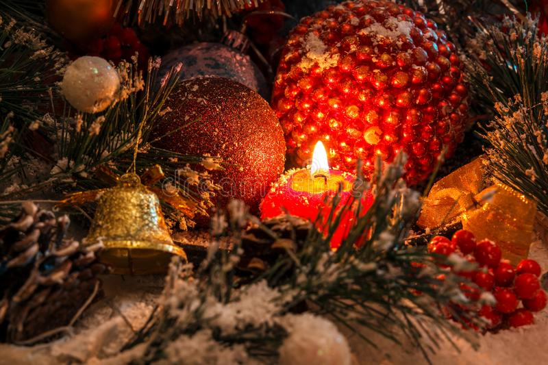 Red Christmas candle on the background of New Year`s decorations and a bell. The magic of Christmas and New Year royalty free stock photo