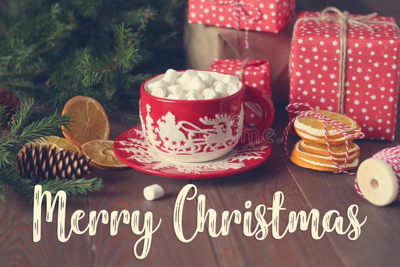 Red Christmas cup with hot cocoa and marshmallows on the wooden table royalty free stock image
