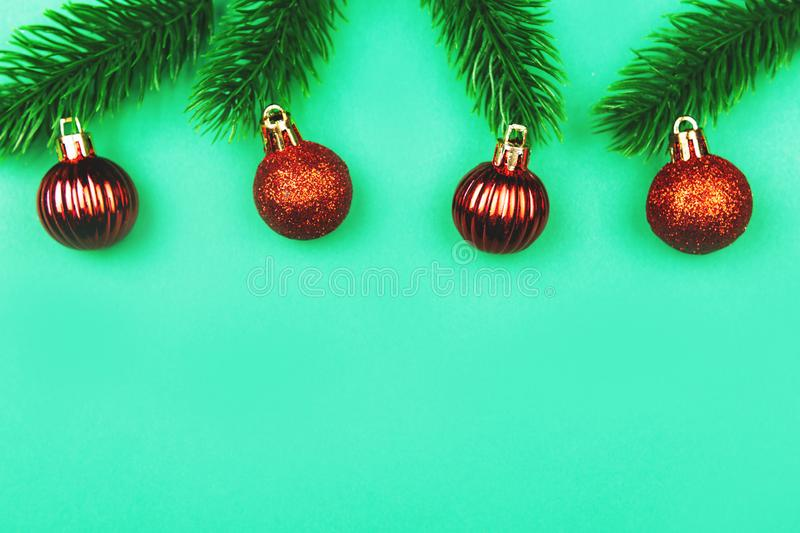 Red Christmas decoration and fir tree branches on green background stock photos