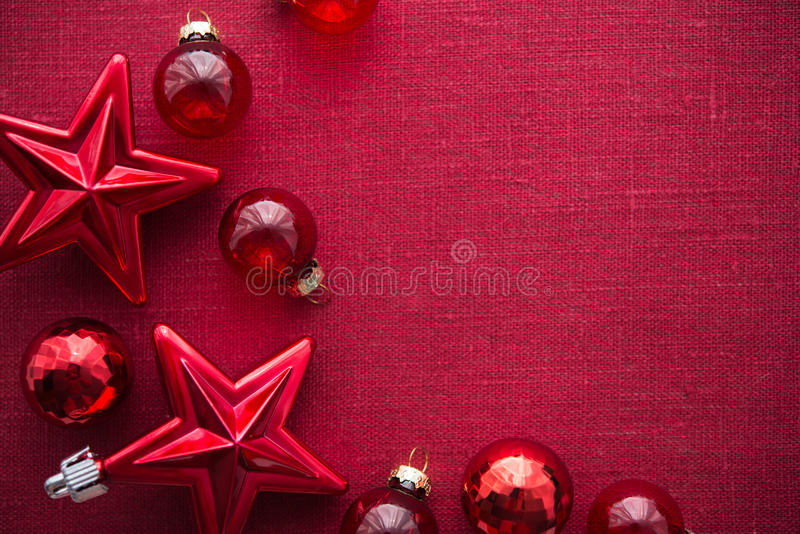 Red christmas decorations (stars and balls) on red canvas background. Merry christmas card. Winter holidays. Xmas theme. Space for text. Happy New Year stock photo
