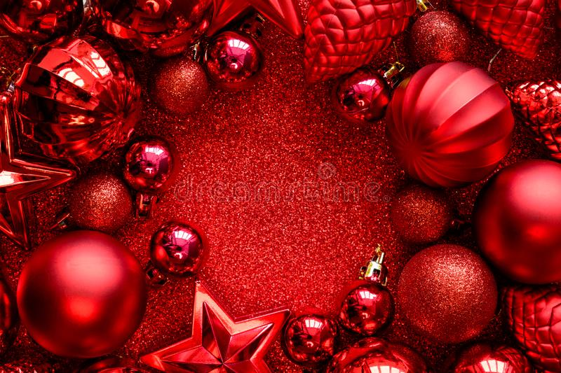 Red Christmas frame. Christmas balls, stars, cones and hearts on red sparkles background. Flat lay. Top view. Copy space stock photo