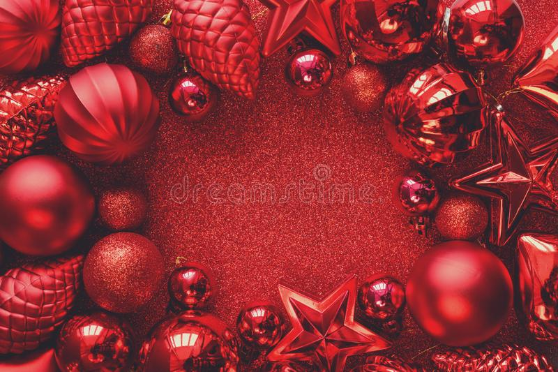 Red Christmas frame. Christmas balls, stars, cones and hearts on red sparkles background. Flat lay. Top view. royalty free stock images