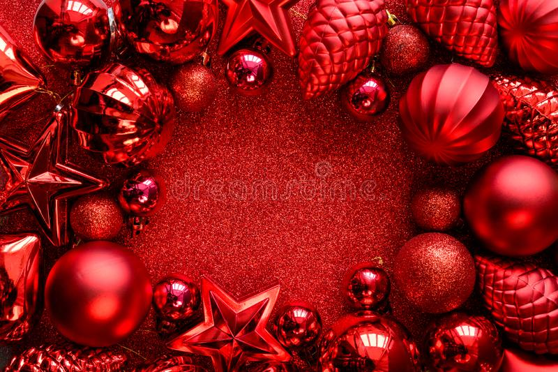 Red Christmas frame. Christmas balls, stars, cones and hearts on red sparkles background. Flat lay. Top view. stock image