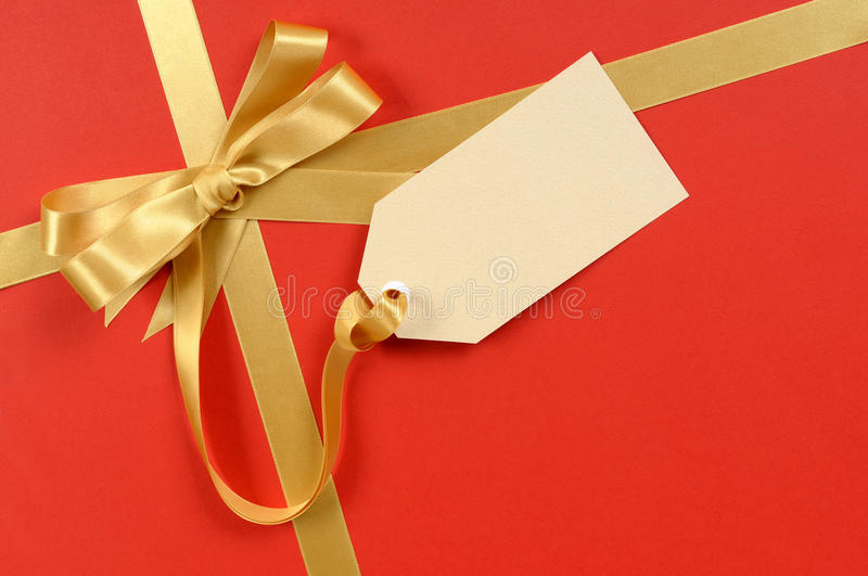 Red Christmas gift background, gold ribbon bow, blank manila gift tag or label stock image