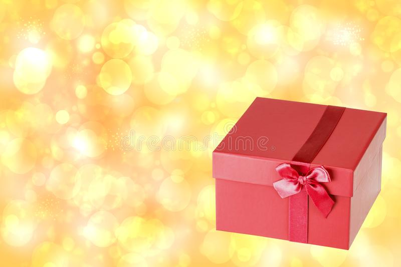 Red christmas gift box on blur golden abstract bokeh background stock photography
