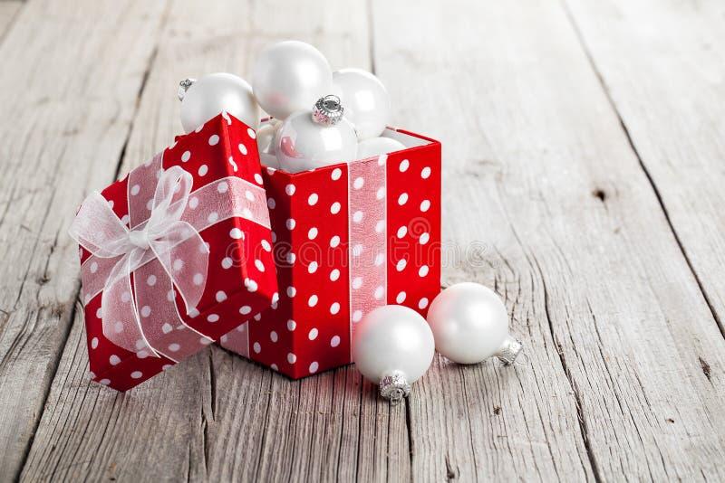 Red Christmas gift box full of xmas white bauble stock photo