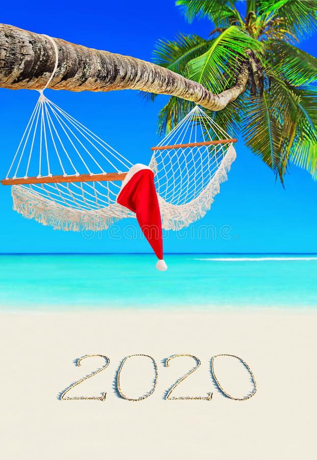 Red Christmas hat on wooden hammock under palm tree at tropical Seychelles beach with happy new year 2020 caption on sand royalty free stock photos
