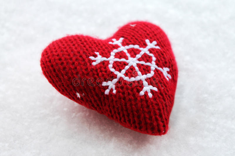Red Christmas heart on the snow. Red knitted Christmas heart on the snow stock photo