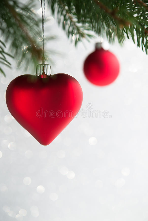 Red christmas ornaments heart and ball on the xmas tree on glitter bokeh background. stock image