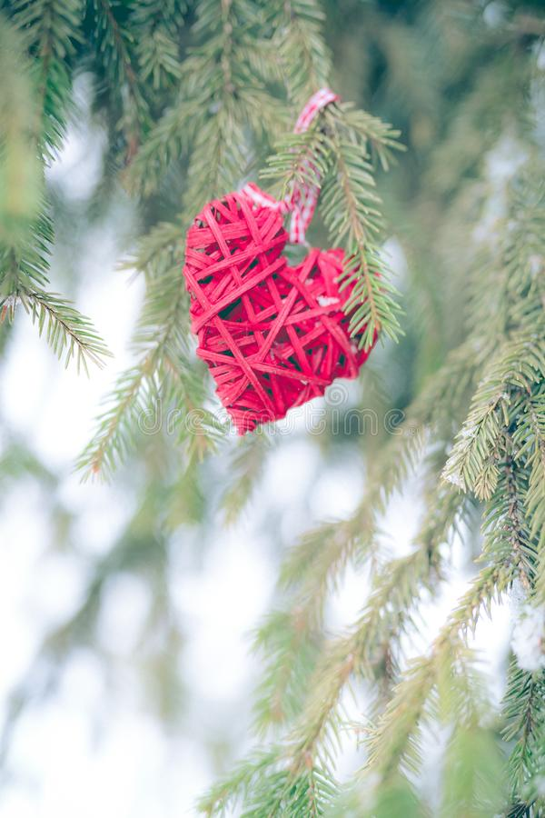 Red Christmas ornaments, heart, on a Christmas tree Merry Christmas greeting card. Winter holiday theme. royalty free stock photo