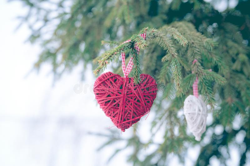 Red Christmas ornaments, heart, on a Christmas tree Merry Christmas greeting card. Winter holiday theme. royalty free stock image