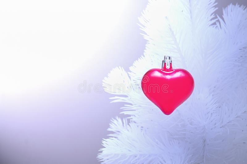 Red christmas ornaments heart, on the white xmas tree on blurry background. Merry christmas card. Winter holiday theme. Happy New royalty free stock images