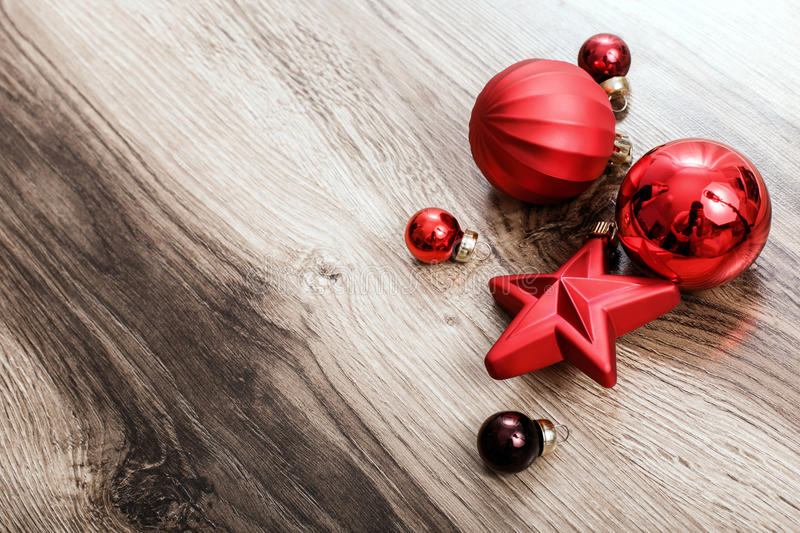 Red Christmas ornaments on a rustic wooden background stock photography
