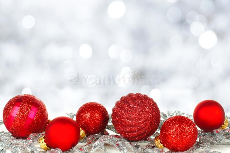 red christmas ornaments with twinkling background stock