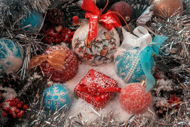 Red Christmas present stands on the snow against a background of a Christmas balls and shiny tinsel stock images