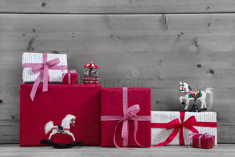 Red Christmas presents and gift boxes with rocking horse on grey. Grey background wood for christmas with red and white gifts and decoration with horses royalty free stock photography