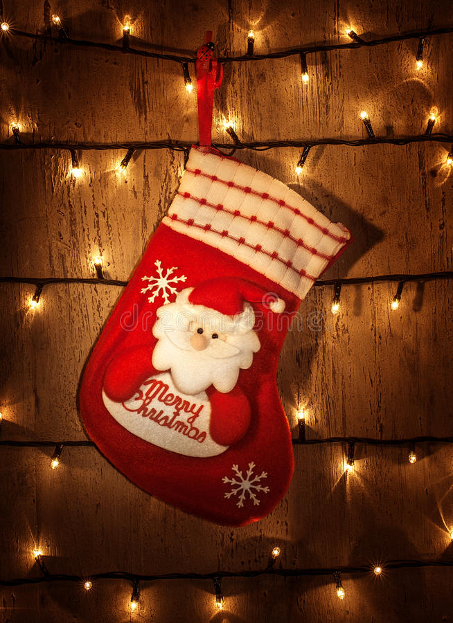 Red Christmas sock. Picture of traditional red Christmas sock hanging on decorated door at home, glowing electrical garland on dark grunge wall, Christmastime stock photos