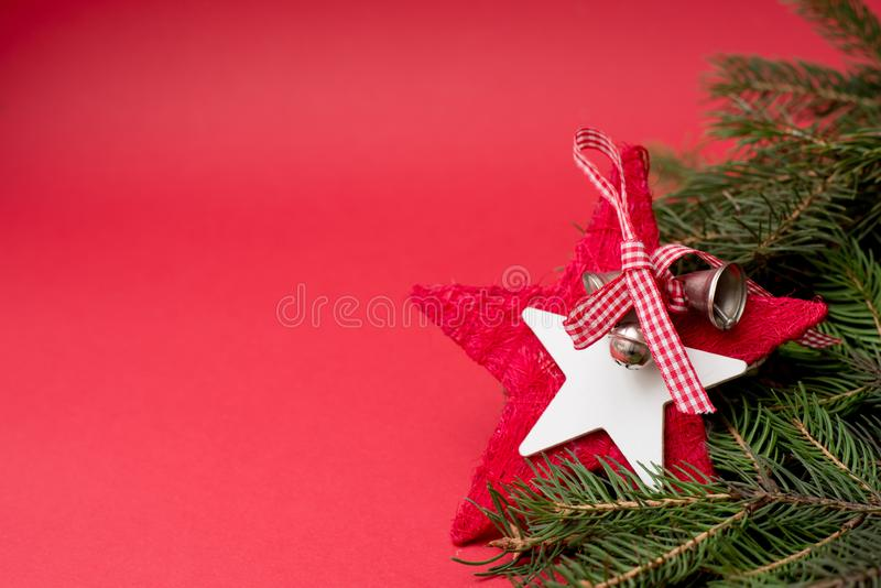 Red christmas star with bells on red background with copy space, new year decor christmas tree. Greeting winter card royalty free stock photography