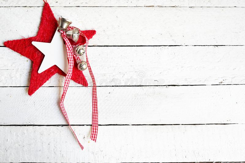 Red christmas star with bells on white wooden background, copy space stock photography