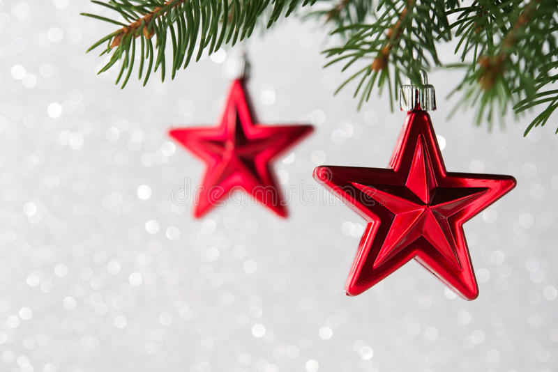 Red christmas stars on the xmas tree on glitter bokeh background. Merry christmas card. stock photo