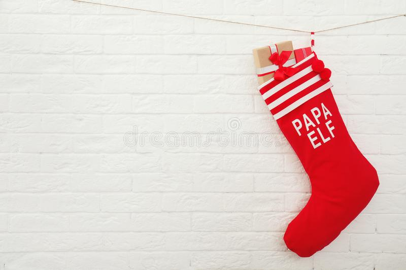 Red Christmas stocking full of gifts hanging on brick wall, space for text. Idea for interior decor royalty free stock photo