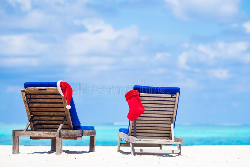Red Christmas stocking and Santa Hat on beach beds. Red santa hat on chair longue at tropical caribbean beach stock photo
