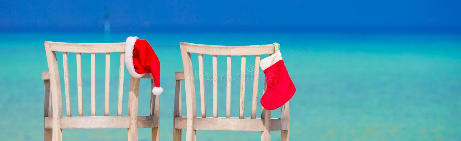 Red Christmas stocking and Santa Hat on chair at tropical white beach. Red santa hat on chair longue at tropical caribbean beach royalty free stock photo