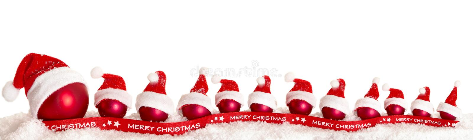 Red Christmas tree balls with Christmas caps in the snow royalty free stock photography