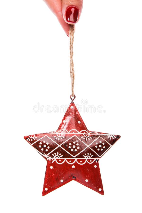 Red christmas tree decor in form of star with ornament. Woman fingers are holding red Christmas tree decor in a form of star with ornament isolated on white royalty free stock image