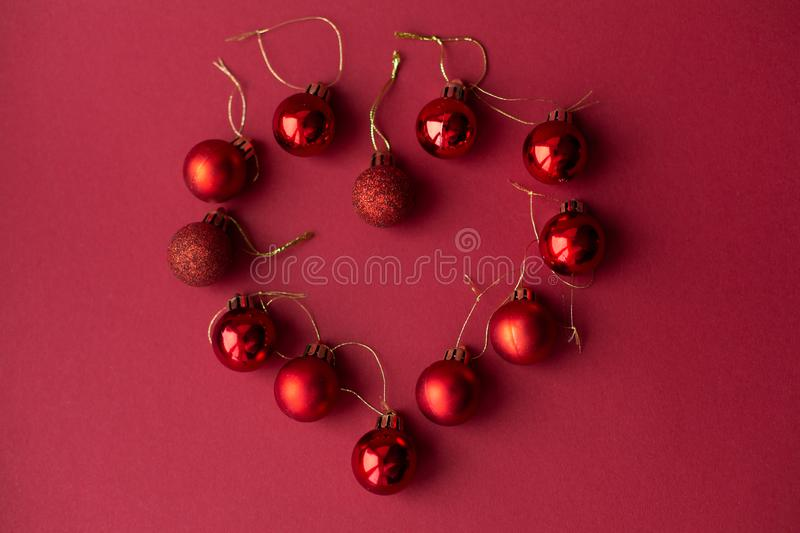 Red Christmas tree decorative toy balls on red celebratory Christmas background laid out in the shape of a heart. New Year`s royalty free stock photo