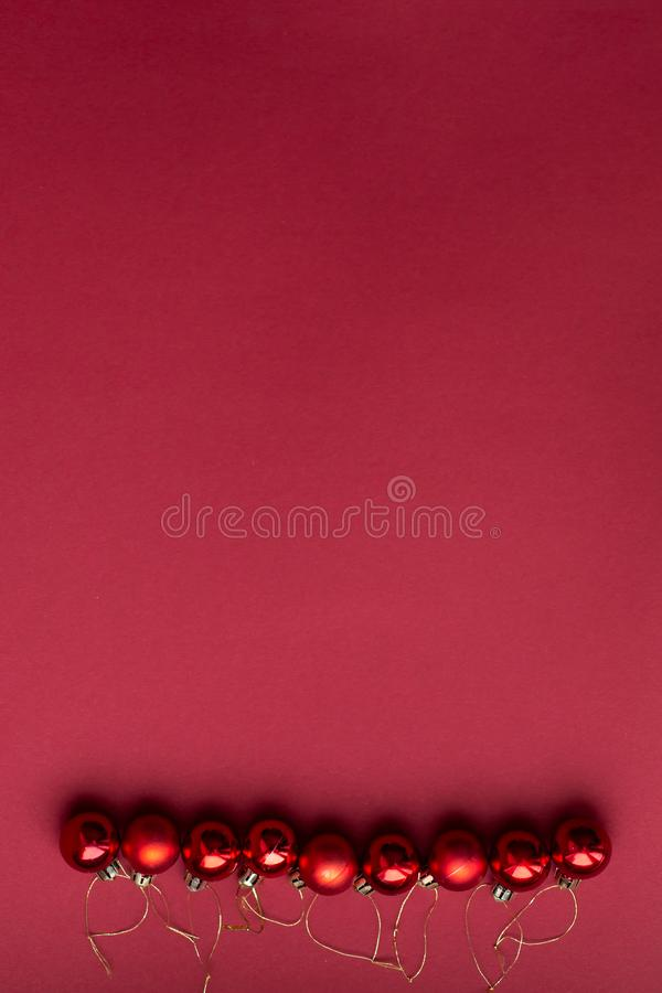 Red Christmas tree decorative toy balls on red celebratory Christmas background laid out in horizontal line. New Year`s holidays. royalty free stock photo