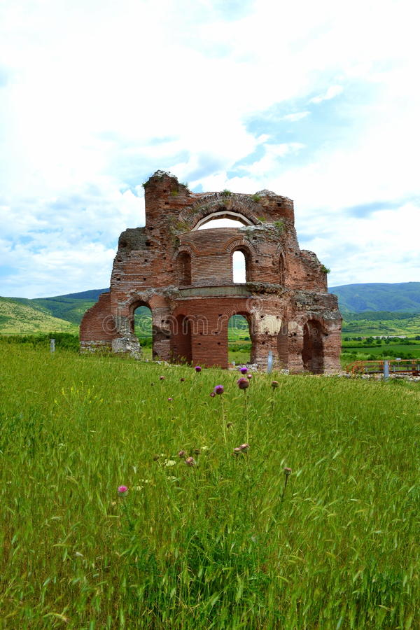 Red church in green grass. The Red Church ruins in green meadow setting,The Red church is the Early Medieval , early Byzantine basilica built in the V-VI century stock photos