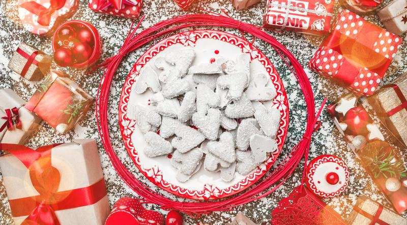 Red circle from decorative wands, with decorative Xmas plate and biscuits, cookies inside, on gray, stone, marble background. Above view, greeting card royalty free stock photography