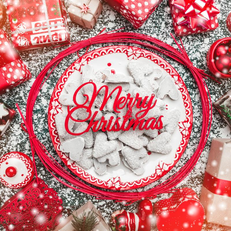 Red circle from decorative wands, with decorative Xmas plate and biscuits, cookies inside, snow effect, marble background. Above view, greeting card royalty free stock images