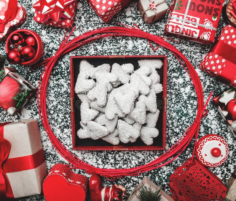 Red circle from decorative wands, with opened black Xmas present box, package and biscuits, cookies inside. On gray, stone, marble background, greeting card royalty free stock images