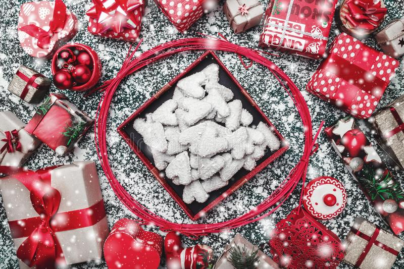 Red circle from decorative wands, with opened black Xmas present box, package and biscuits, cookies inside. Snow effect, marble background, greeting card stock photography
