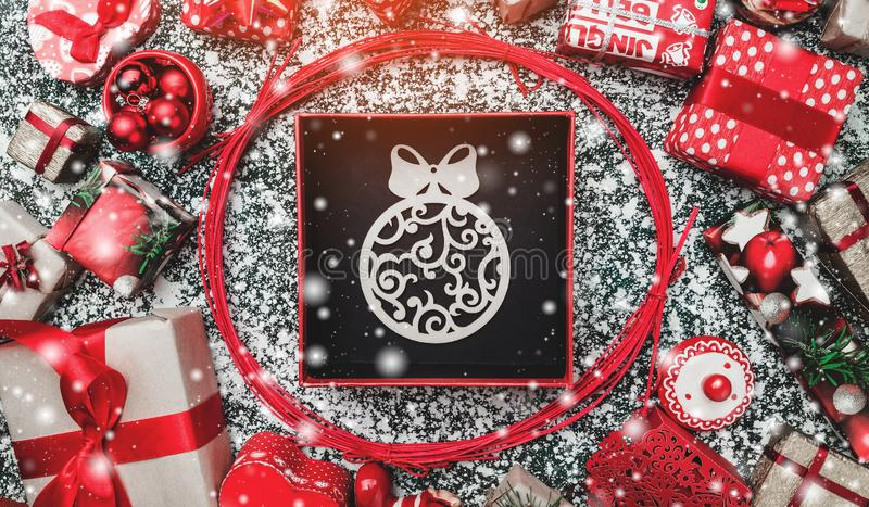 Red circle from decorative wands, with opened black Xmas present box, package and handmade wooden globe inside, snow effect. Marble background, greeting card royalty free stock photography