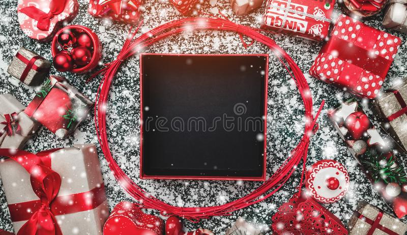 Red circle from decorative wands, with opened black Xmas present box, package and space for text writing inside. On gray, stone, marble background, snow effect royalty free stock photos