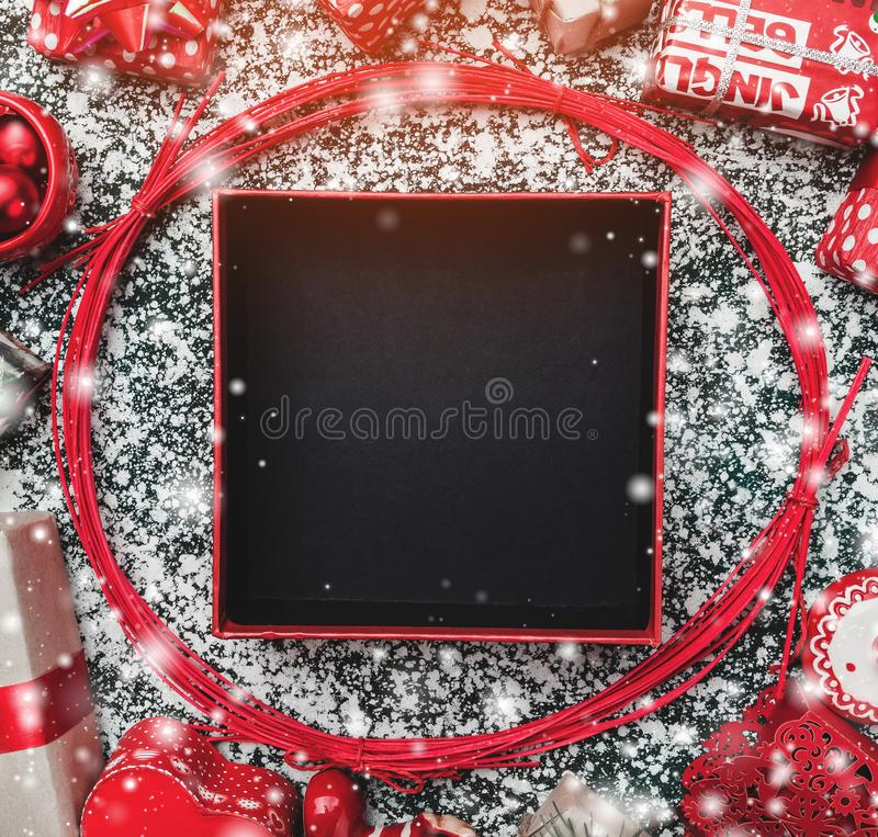 Red circle from decorative wands, with opened black Xmas present box, snow effect, on gray, stone, marble background. Greeting card royalty free stock image