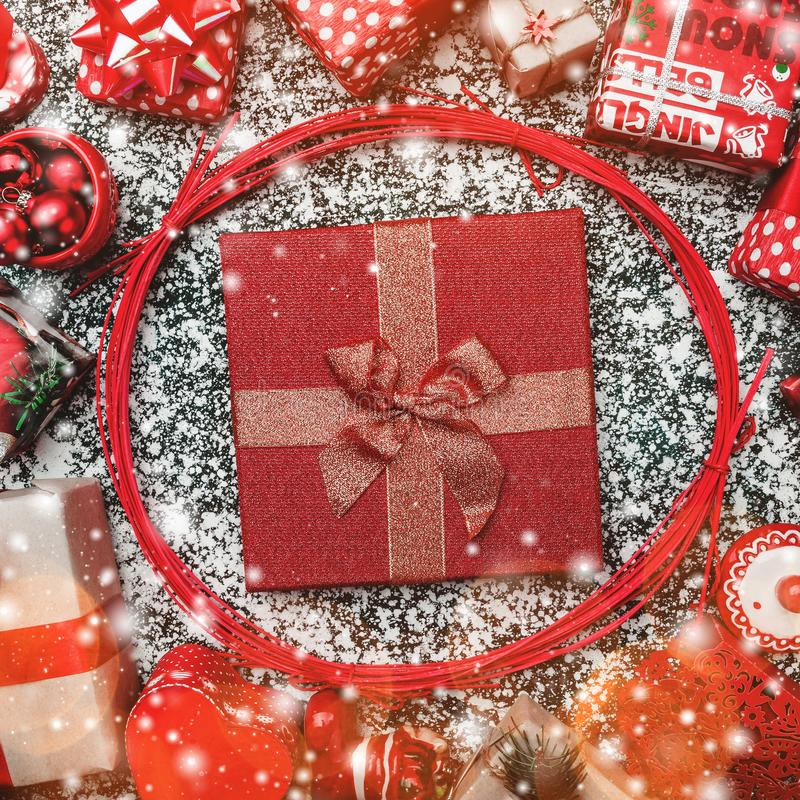 Red circle from decorative wands, with Xmas present box, package inside, on gray, blush and snow effect. Marble background, greeting card stock photos