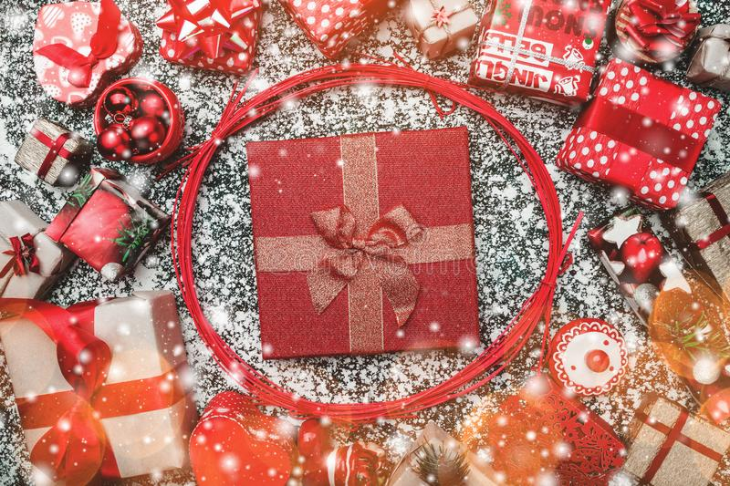 Red circle from decorative wands, with Xmas present box, package inside, on gray, snow effect, marble background. Greeting card stock images