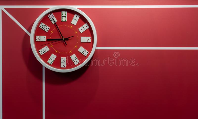 Red circle wall clock decorated with domino pieces hanging against red wall with graphic line background stock photo