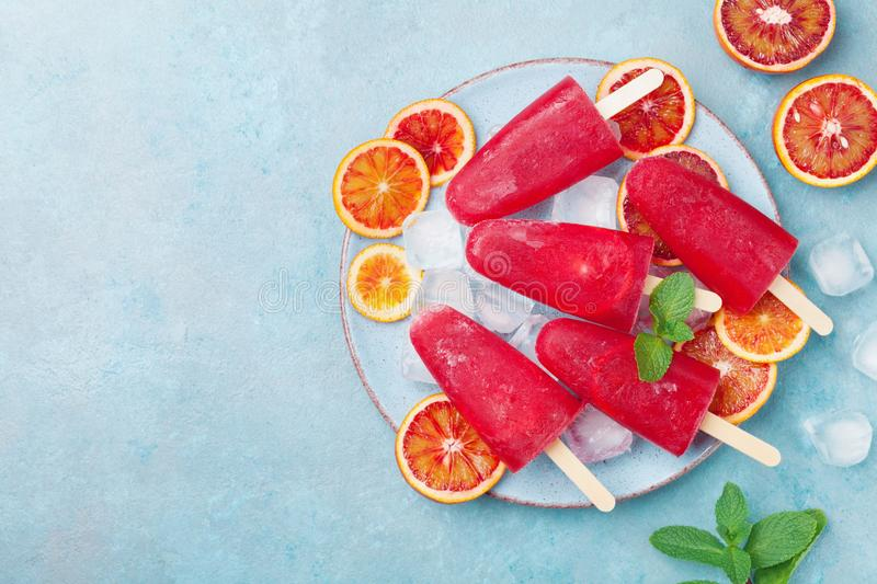 Red citrus ice cream or popsicles decorated mint leaves and orange slices on blue table from above. Frozen fruit juice. royalty free stock images