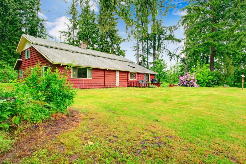 Red clapboard siding house. Clapboard siding house with walkout deck. Backyard view of lawn, blooming bushes and trees royalty free stock photography