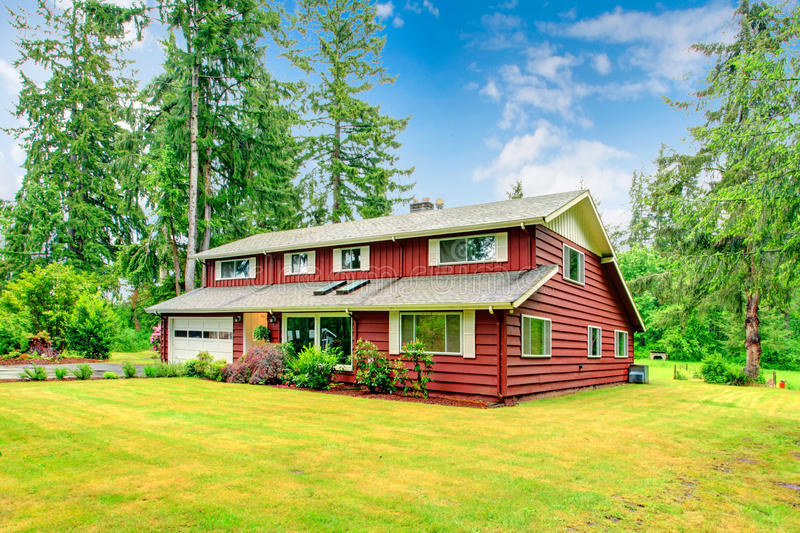 Red clapboard siding house. With white garage door, and white shutters. View of green lawn with blooming flower bed stock photography