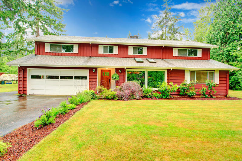Red clapboard siding house. With white garage door, and white shutters. View of wet driveway and green lawn with blooming flower bed stock images