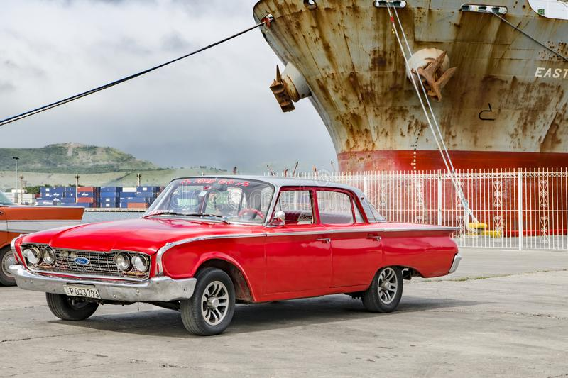 Red classic american car - Ford - in front of rusty ship in harbor of Santiago de Cuba stock image