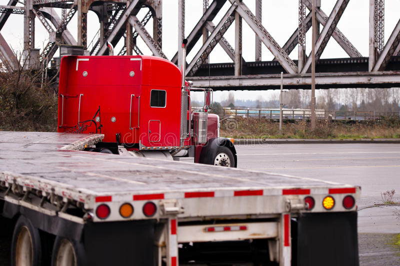 Red classic big rig truck old bridge flat beds turning on road royalty free stock photography