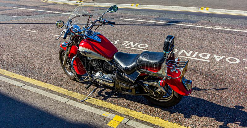 A red classic Kawasaki motorcycle parked on a street royalty free stock images